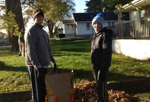 Students from Brother Rice High School help with a fall clean up for a local senior.